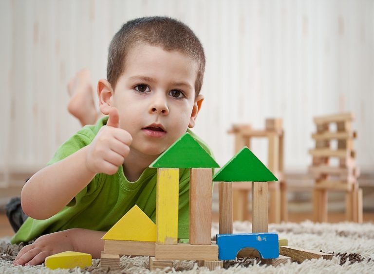 little boy building a house with colorful wooden blocks